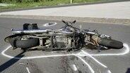 Ein Motorrad liegt nach einem Unfall auf der Straße. © Nord-West-Media TV Foto: Nord-West-Media TV