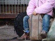 Ein Kind sitzt auf einem vollbepackten Koffer in der Erstaufnahme für Flüchtlinge in Osnabrück.  Fotograf: Kora Blanken