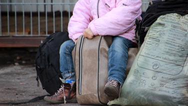 Ein Kind sitzt auf einem vollbepackten Koffer in der Erstaufnahme für Flüchtlinge in Osnabrück.  Foto: Kora Blanken