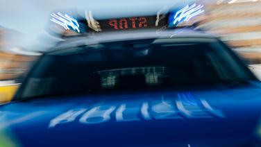 Ein mit Bewegungsunschärfe fotografiertes Polizeiauto mit Blaulicht und Stop in der Anzeigetafel. © NDR Foto: Julius Matuschik
