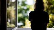 Eine Frau steht in ihrer Wohnung an einem Fenster. © picture alliance/dpa Foto: Fabian Sommer