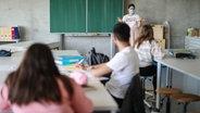 Un enseignant enseigne aux élèves avec un masque.  © photo alliance Photo: Christoph Schmidt