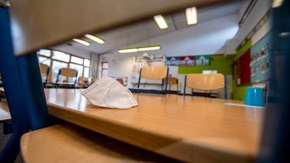 Eine FFP2-Maske liegt auf einem hochgestellten Stuhl in einem Klassenzimmer. Themenbild: Corona und Schule © picture alliance / Inderlied/Kirchner-Media | Inderlied/Kirchner-Media Foto: Inderlied/Kirchner-Media