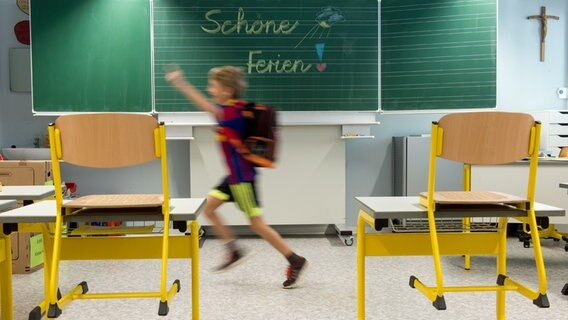 """Ein Junge läuft in einem Klassenzimmer vor einer Tafel mit der Aufschrift """"Schöne Ferien"""". © picture-alliance/dpa Foto: Armin Weigel"""