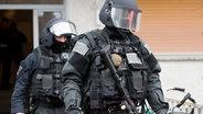 Beamte des Spezialeinsatzkommandos (SEK) der Polizei verlassen ein Wohnhaus. © dpa Foto:  Boris Roessler