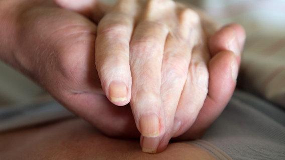 The hand of a nurse holds the hand of an old woman.  © dpa - Bildfunk Photo: Sebastian Kahnert