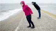 Eine Frau und ein Mann lehnen sich in den Wind.
