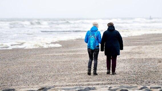 Two women walk on a beach on the North Sea.  © dpa-Bildfunk Photo: Hauke-Christian Dittrich