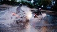 Zwei Motorrollerfahrer fahren bei einem schweren Unwetter mit Starkregen über eine überflutete Straße in Sehnde in der Region Hannover. © dpa - Bildfunk Fotograf: Julian Stratenschulte