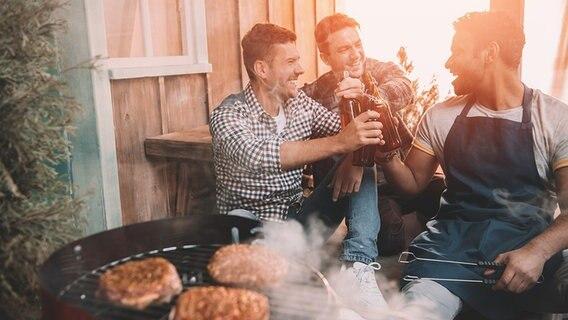 Männer trinken vor einem Grill Bier in geselliger Runde. © fotolia Fotograf: LIGHTFIELD STUDIOS