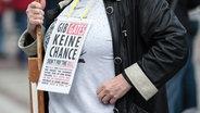 """Eine Frau auf einer Demo der Initiative """"Querdenken"""" hat ein Schuild mit der Aufschrift """"Gib Gates keine Chance - don't pay the Bill"""" um den Hals gehängt. © picture alliance Foto: Dennis Ewert"""