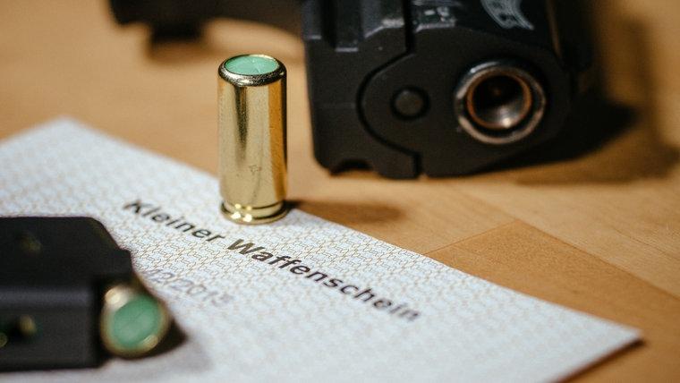 Ein kleiner Waffenschein liegt zwischen einer Schreckschuss-Pistole «Walther P22», einem Magazin und einer Platzpatrone. © dpa Foto: Oliver Killig