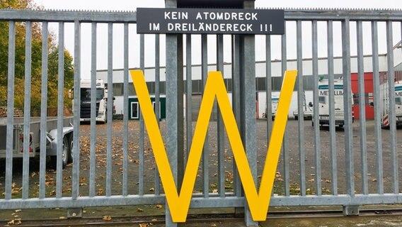 """Ein gelbes """"W"""" an einem Metallzaun. Darüber ein Schild """"Kein Atomdreck im Dreiländereck"""". © NDR Foto: Julia Henke"""