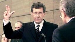 Der damals neue niedersächsische Ministerpräsident Christian Wulff (CDU) leistet am 4.3.2003 im Landtag von Hannover seinen Amtseid vor dem neuen Landtagspräsicenten Jürgen Gansäuer.  © picture-alliance / dpa Fotoreport Foto: Wolfgang Weihs