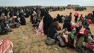 Auf einer großen Freifläche im syrischen Baghouz stehen und sitzen viele Frauen und Kinder. © dpa picture alliance/Le Pictorium Foto: Chris Huby