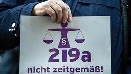 """Eine Frau hält bei einer Kundgebung einen Zettel mit der Aufschrift """"219a nicht zeitgemäß!"""". © dpa picture alliance Foto: Silas Stein"""