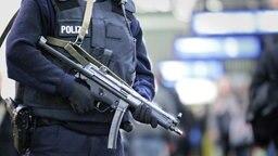 Bewaffneter Polizist mit Sicherheitsweste © picture alliance / dpa Fotograf: Bodo Marks