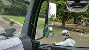 Eine junge Radfahrerin ist rechts neben einem Lkw auf der Straße zu sehen. Das Foto ist vom Fahrersitz des Lkw aufgenommen worden. © dpa picture alliance
