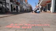 Auf dem Gehweg der Fußgängerzone wird auf die Abstandsregeln hingewiesen. Foto: Sebastian Böhme