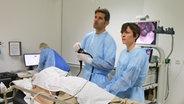 Assistenzärztin Rahel Meier und Oberarzt Malte Kasparek untersuchen einen Patienten. © NDR Foto: Sofia Tchernomordik