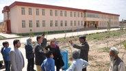 Eine Gruppe von Menschen stehen vor einer afghanischen Schule und unterhalten sich.  Foto: Marga Flader