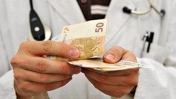 Ein Arzt zählt Geldscheine. © dpa Fotograf: Tobias Hase