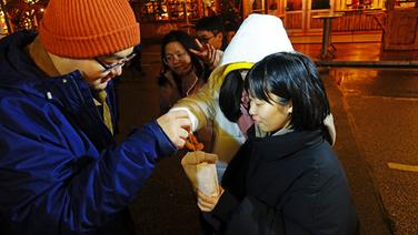 Chinesische Austauschstudenten nehmen sich auf dem Weihnachtsmarkt in Heide Schmalzgebäck aus einer Tüte. | NDR