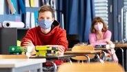 Die Schüler sitzen im Klassenraum und tragen einen Mund-Nase-Schutz. © Picture Allaince Foto: Sven Hoppe