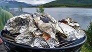 Auf einem Grill liegt Fisch in Alufolie © NDR Fotograf: Sven Brüggemann