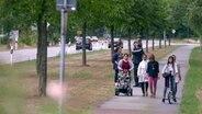 Eine Flüchtlingsfamilie läuft an einer Straße entlang. © NDR