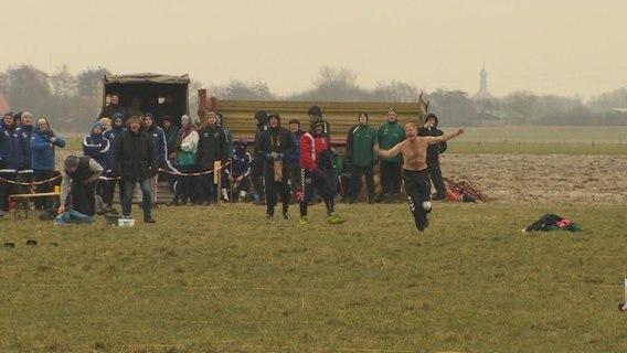 Eine Gruppe von Boßel-Fans stehen auf einem Feld. © NDR