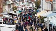 Leute laufen durch die Fußgängerzone in Büsum. Foto: Manngold