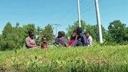 Eine Familie aus Sierra Leone sitzt im Gras.