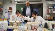 Le professeur Rolf Hilgenfeld de l'Université de Lübeck regarde par-dessus les épaules des deux chercheurs Xinyuanyuan Sun et Linlin Zhang au travail. © Linda Eberlin Photo: Linda Eberlin