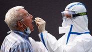 Ein Mann lässt sich an einer mobilen Teststation auf das Coronavirus testen. © dpa-Bildfunk Foto: Daniel Reinhardt/dpa