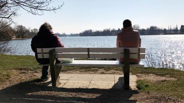Zwei Frauen sitzen mit einem Sicherheitsabstand von ungefähr zwei Metern nebeneinander auf einer Bank in der Natur und unterhalten sich. | NDR