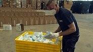 Ein Mann packt Schutzmasken aus einem gelben Behälter in Versand-Kartons. © NDR