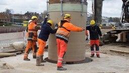 Vier Bauarbeiter lassen den Stahlschacht für den Tunnel in den Boden gelassen. © Wasser- und Schifffahrtsamt Kiel-Holtenau Fotograf: Georg Lindner