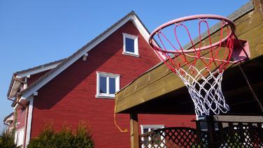 Ein Basketballkorb im Vordergrund eines Einfamilienhauses. © NDR Fotograf: Hauke Bülow