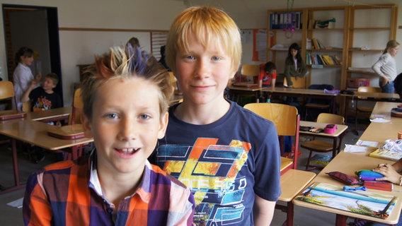"""Zwei Jungen in ihrem Klassenzimmer Ben (9 Jahre) (links) hat sich seinen Pony frisch gefärbt in den Farben von seinem Lieblingsverein Olympia Bad Schwartau. """"In den Ferien fahr ich nach Berlin und hab in der vierten Woche die Meerschweinchen aus unserer Klasse."""" Sein Klassenkamerad Maximo (11 Jahre) (rechts) plant einen großen Urlaub. """"In der zweiten Ferienwoche fahr ich mit meiner Familie nach Schweden. Am meisten freu ich mich auf's Angeln."""" © NDR Foto: Charlotte Horn"""