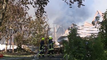 Mehrere Feuerwehrleute löschen einen brennende Bauernhof.   Westkuesten-News
