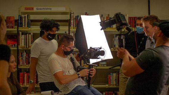 Louis Bennies mit der Kamera am Filmset im Hintergrund hält eine Person ein Licht fest. © Louis Bennies