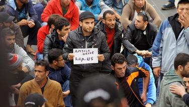 """Ein Flüchtling hält am 08.09.2015 auf dem Lübecker Hauptbahnhof ein Schild mit der Aufschrift """"Angela Merkel, help us"""" in die Luft. © NDR Foto: Katrin Bohlmann"""