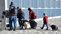 Eine fünf-köpfige Flüchtlingsfamilie betritt für die freiwillige Ausreise mit ihrem Gepäck einen Flughafen. © dpa - Bildfunk Fotograf: Uwe Zucchi
