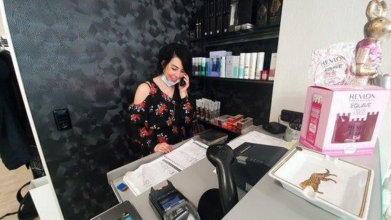 Salonchefin Julia Krieger telefoniert. © NDR Foto: Sebastian Parzanny