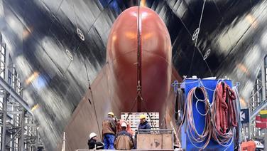 """Werftarbeiter stehen vor dem Stapellauf der Fähre """"Gardenia Seaways"""" auf der Werft der Flensburger Schiffbaugesellschaft. © dpa-Bildfunk Foto: Carsten Rehder/dpa"""