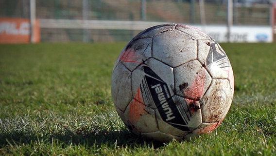 Ein Fußball liegt auf einem Fußballplatz. © NDR Foto: Janis Röhlig