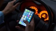 Ein Mann sitzt in einem Auto am Steuer und hält ein Smartphone in der Hand. © dpa-Bildfunk Fotograf: Monika Skolimowska