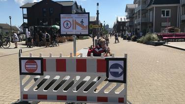 Warnschilder stehen an einer Promenade in Heiligenhafen bei Sonnenschein. | NDR