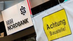 Blick auf einen Eingang zur HSH Nordbank, neben deren Eingang ein Schild Achtung Baustelle! häng. © dpa/picture alliance Fotograf: Daniel Bockwoldt